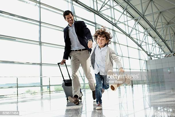 Father and son (5-6) running across airport lobby