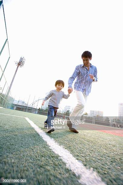 Father and son (2-4) running across sports field, holding hands