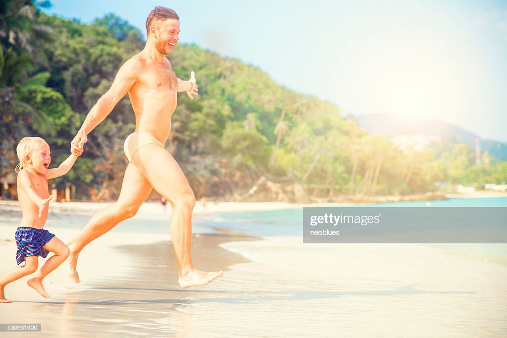 Father And Son Running Along Beach : Stock Photo