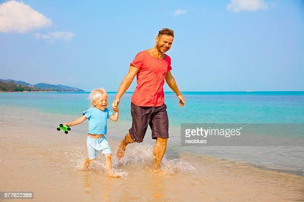 Père et fils courir le long de la plage