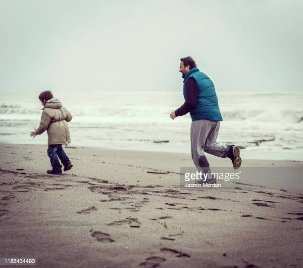 father and son running and walking on winter beach - jasmin sturm stock-fotos und bilder