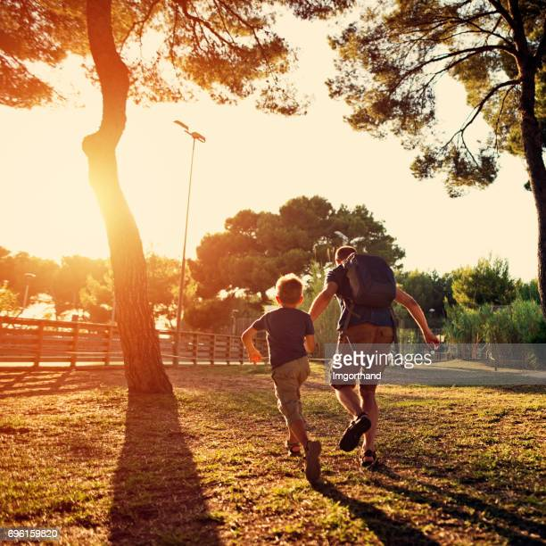 father and son running in the city park - human back stock pictures, royalty-free photos & images