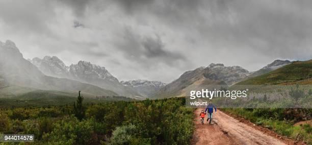 Vater und Sohn laufen zusammen zwischen Snow capped Berge