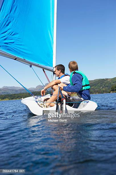 Father and son (11-13) sailing in dinghy on lake