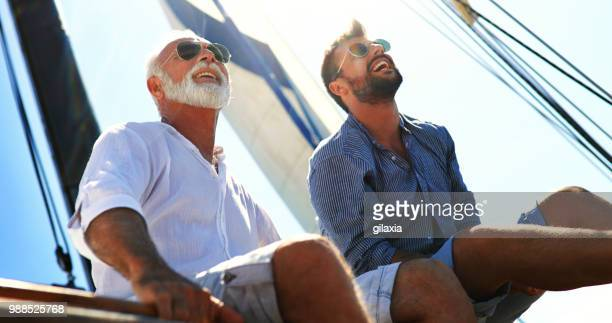 father and son sailing. - boat stock pictures, royalty-free photos & images