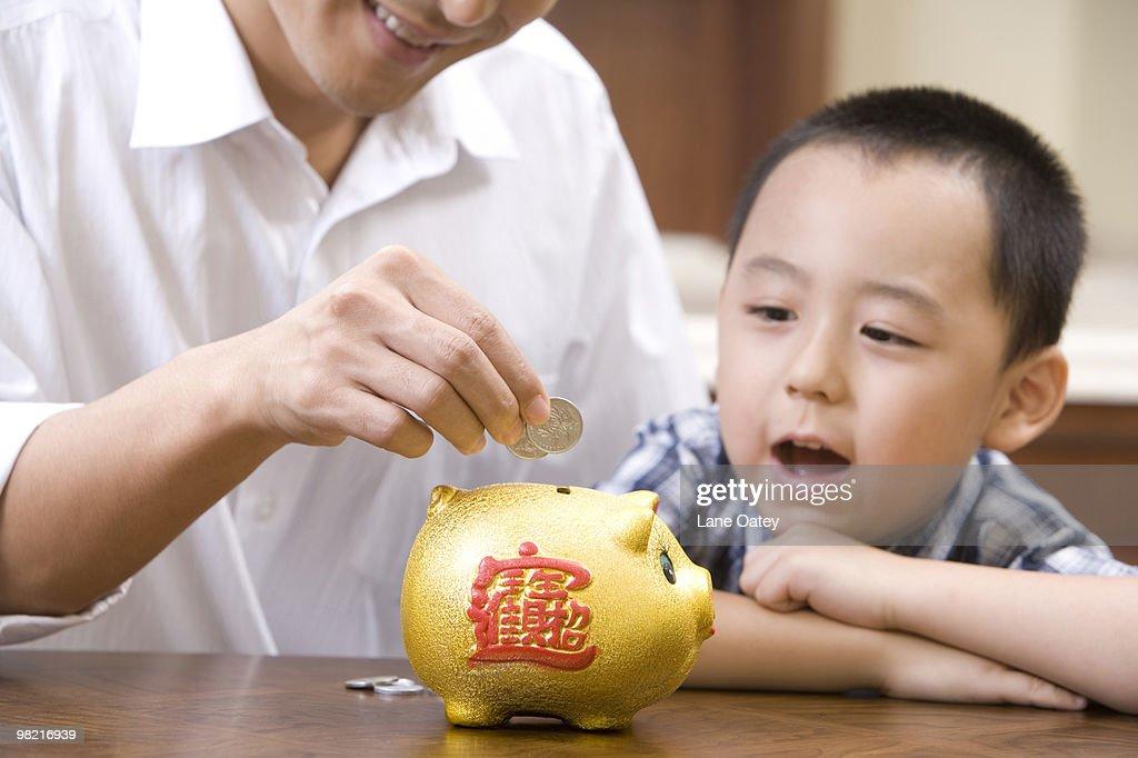 Father and son saving coins into a piggy bank : Stock Photo