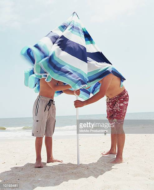 Father and son securing beach umbrella