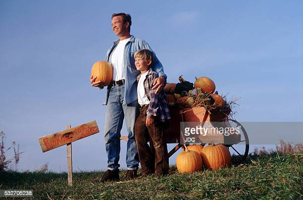 Father and son selling pumpkins