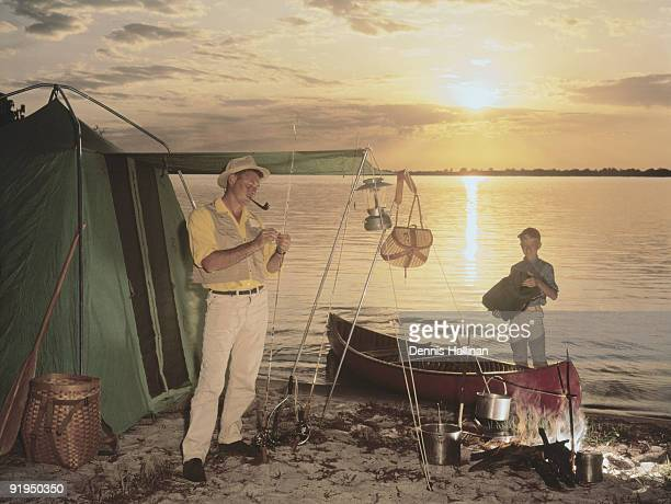 Father and son setting up lakeside camp at sunset