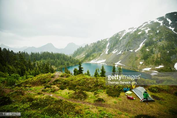 father and son setting up tent above alpine lake during backpacking trip in rain - washington state stock pictures, royalty-free photos & images