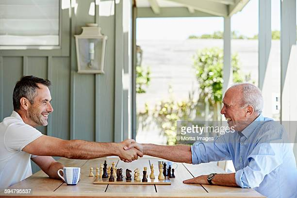 Father and son shaking hands over chess set