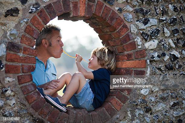 father and son share some sweets - chert stock photos and pictures