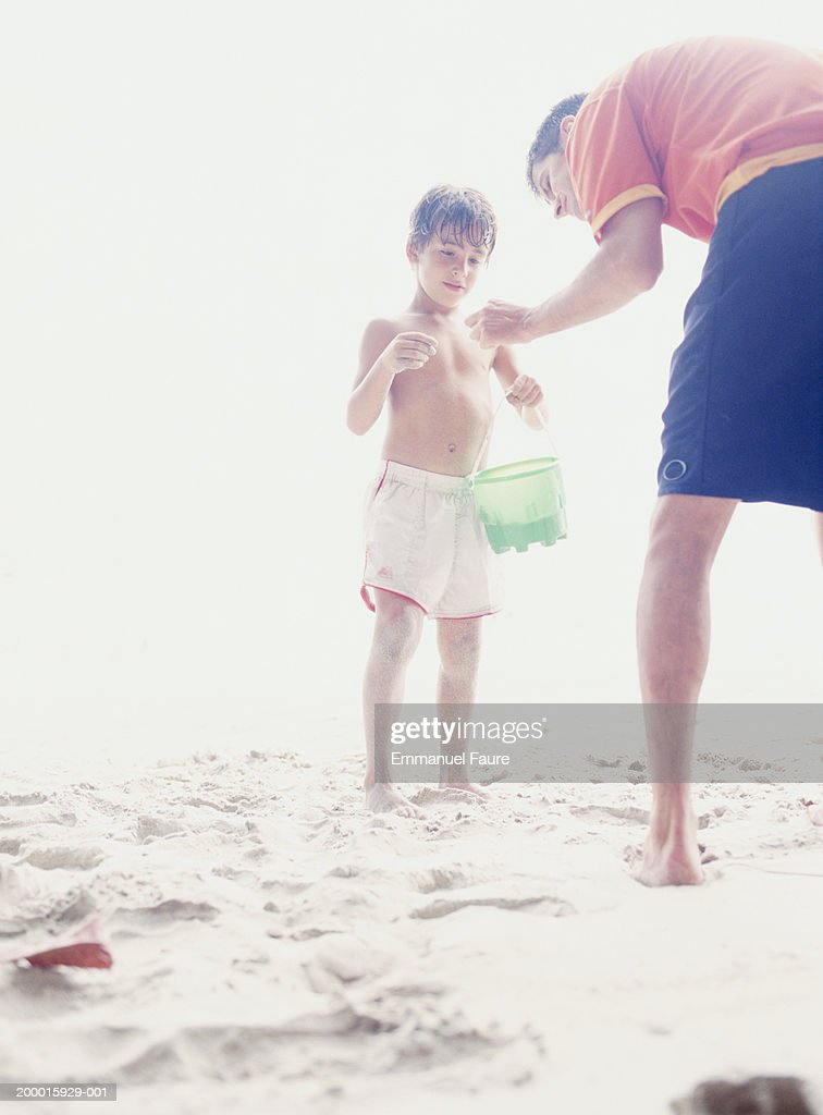 Father and son (6-8) sharing discovery on beach : Stock Photo