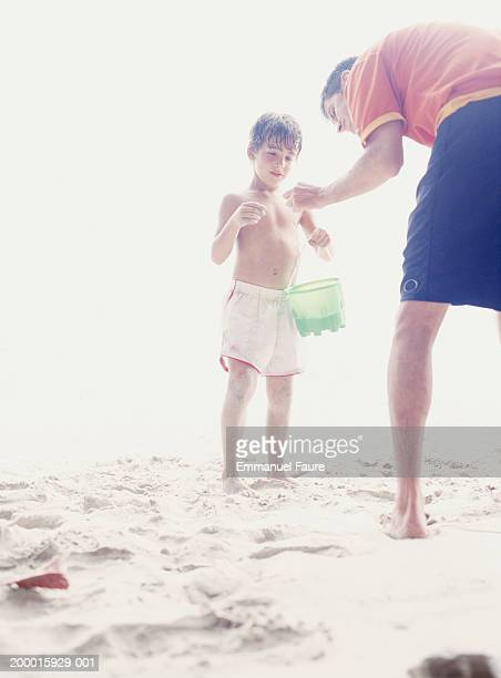 father and son (6-8) sharing discovery on beach - overexposed stock photos and pictures