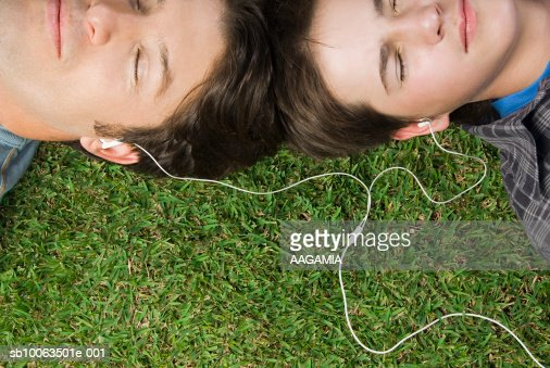 Father And Son Sharing Mp3 Player Lying On Grass Elevated