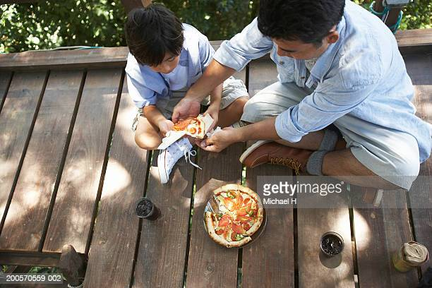 Father and son (8-9) sharing pizza in tree house, elevated view