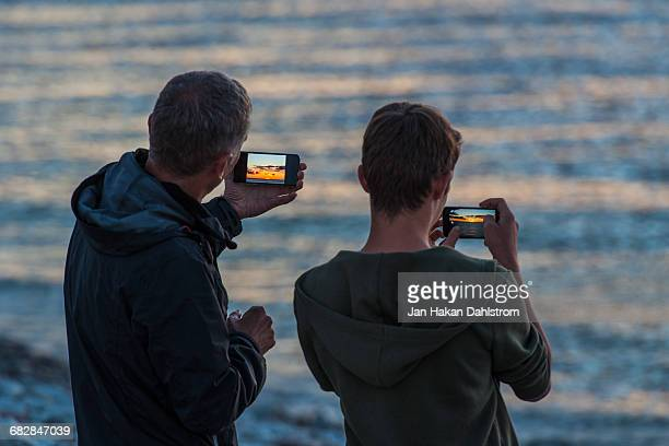 Father and son shooting sunset with cell phones