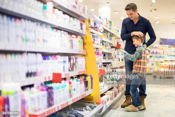 father and son shopping for cosmetics - grooming product stock photos and pictures