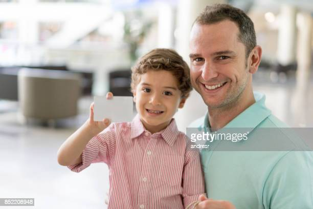 Father and son shopping with a credit card at the mall