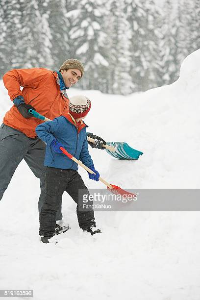 Father and son shoveling snow