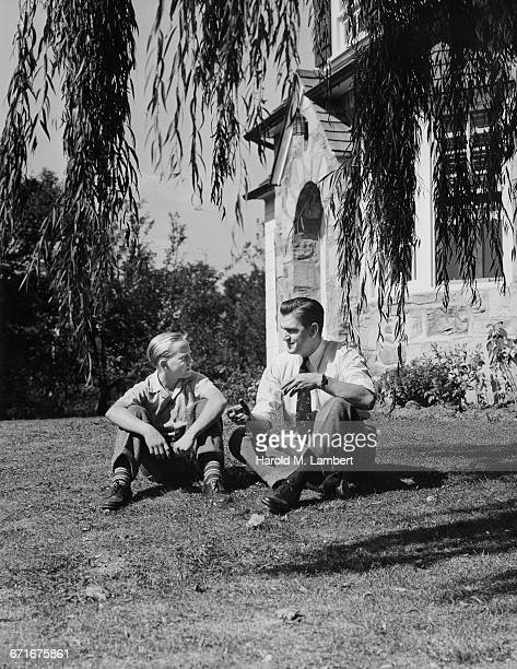 father and son sitting and talking  - {{ contactusnotification.cta }} stockfoto's en -beelden