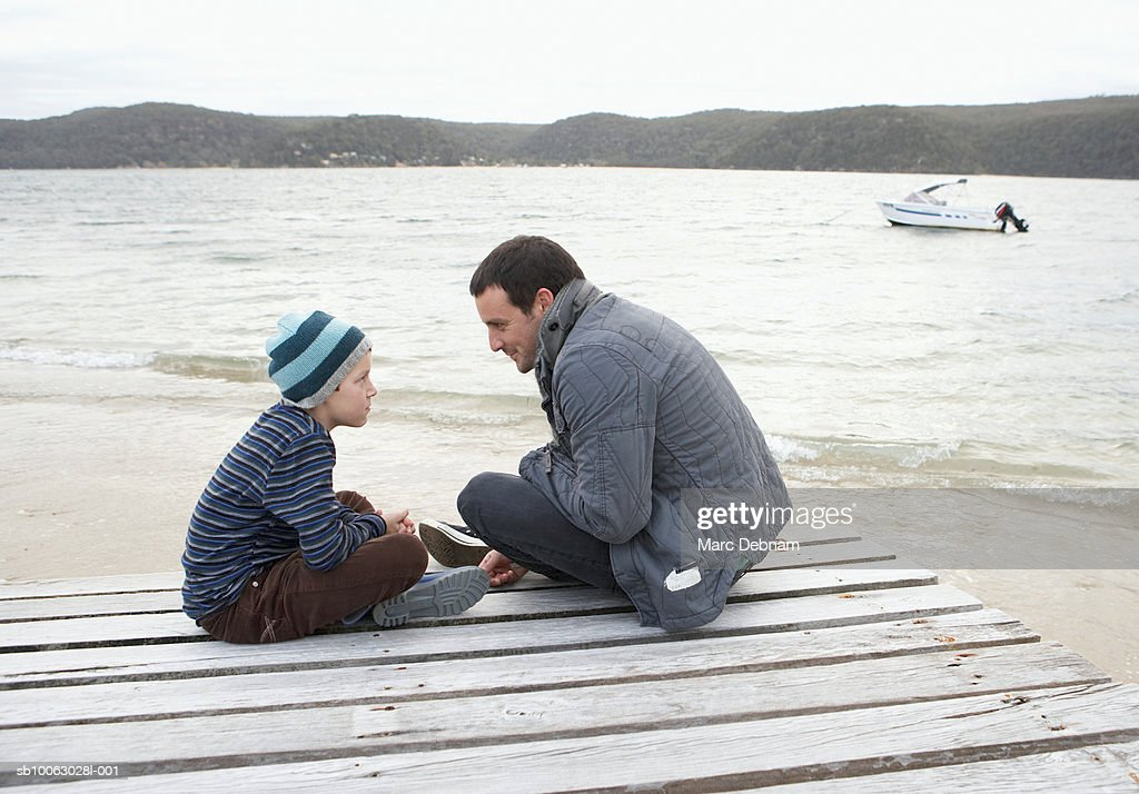 Father and son (10-11) sitting at end of dock at edge of lake, talking, side view : Stock Photo