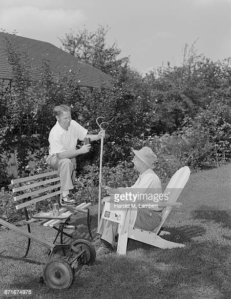 father and son sitting in garden and drinking - {{ contactusnotification.cta }} stockfoto's en -beelden