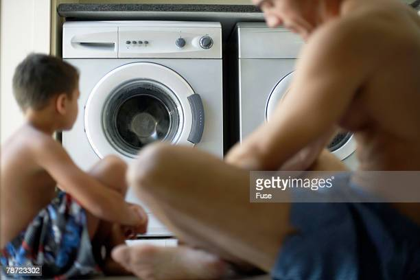 Father and Son Sitting in Laundry Room