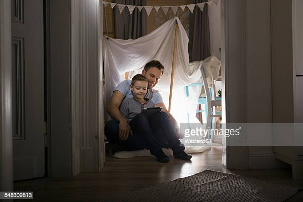 Father and son sitting in self-made tent at home in the evening using digital tablet
