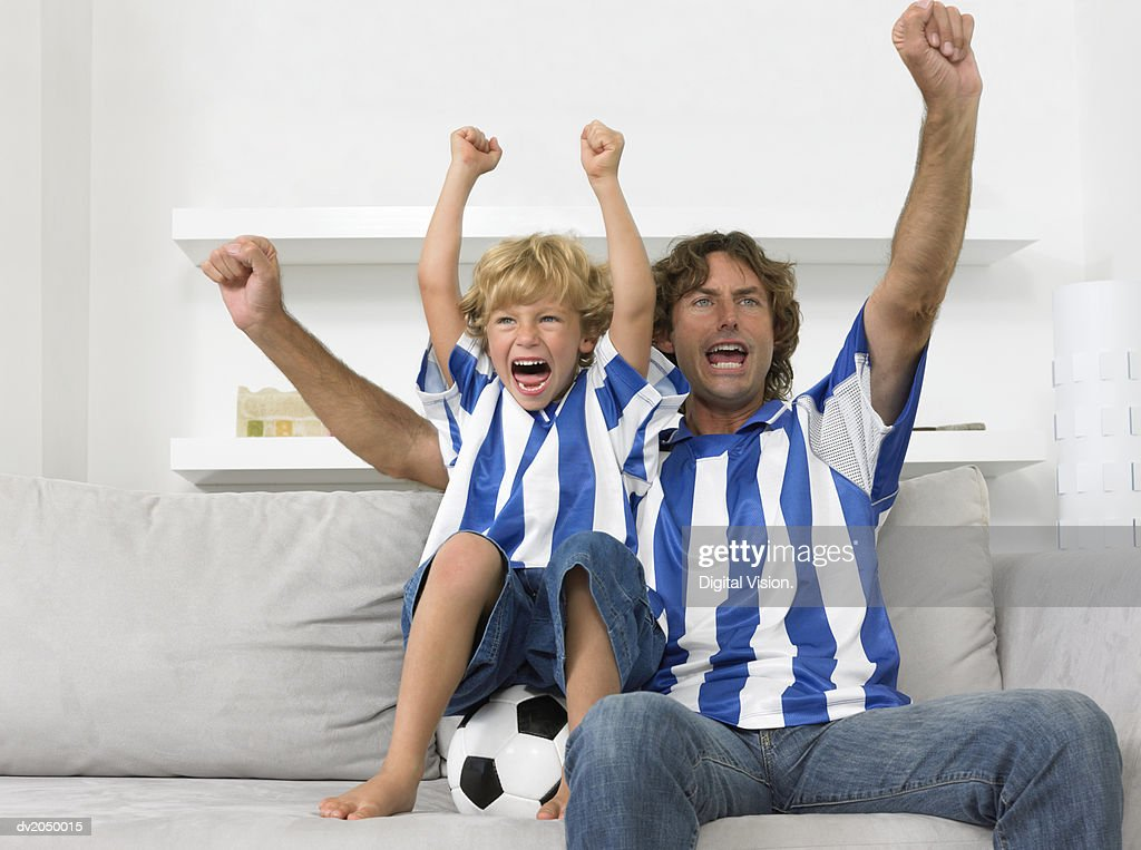 Father and Son Sitting on a Sofa, Wearing Football Strips and Cheering : Photo