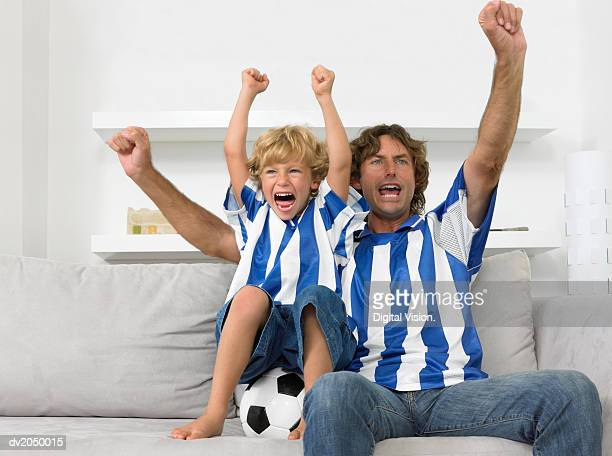 father and son sitting on a sofa, wearing football strips and cheering - trikot stock-fotos und bilder