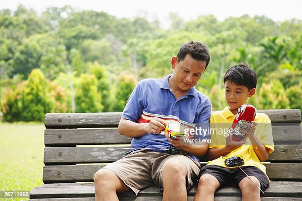 father and son, sitting on bench, holding remote control cars - remote controlled stock photos and pictures