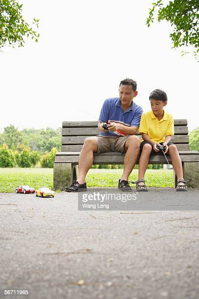 father and son, sitting on bench, playing with remote control cars - remote control car games stock pictures, royalty-free photos & images