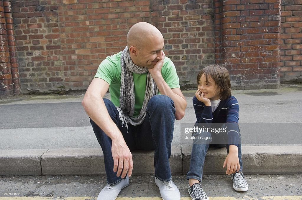 Father and son sitting on curb : Stock Photo