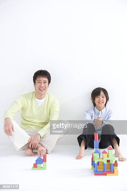 Father and son (8-9) sitting on floor side by side