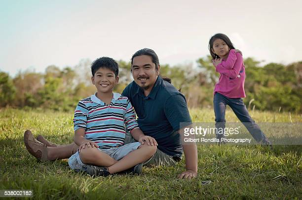 Father and son sitting on ground
