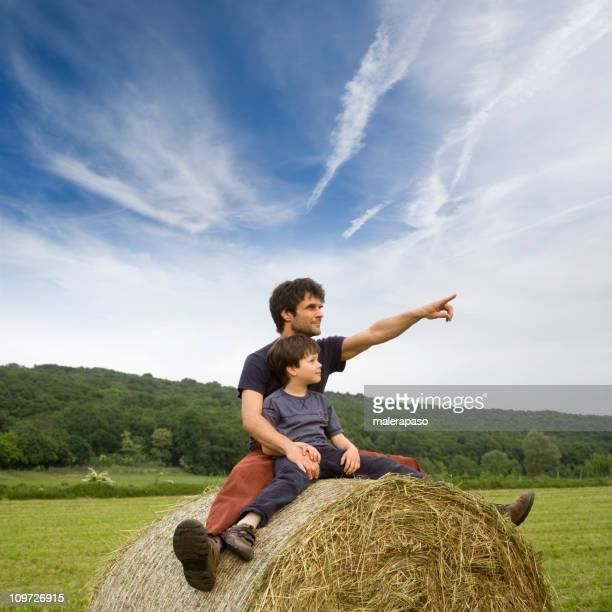 Father and Son Sitting on Hay Bale