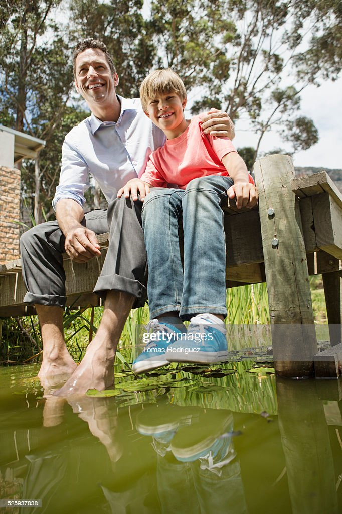 Father and son (10-12) sitting on jetty : Stock Photo