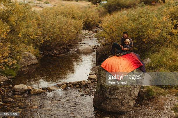 Father and son sitting on rock beside creek, father teaching son to fish, Mineral King, Sequoia National Park, California, USA