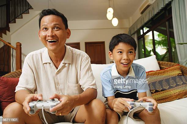 Father and son, sitting on sofa, holding video game controllers