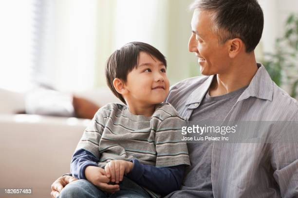 Father and son sitting on sofa together