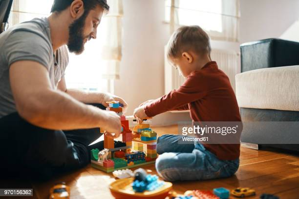 father and son sitting on the floor playing together with building bricks - juguete fotografías e imágenes de stock