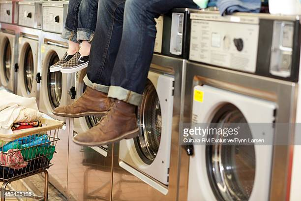 Father and son sitting on top of washing machines in launderette, cropped shot of legs