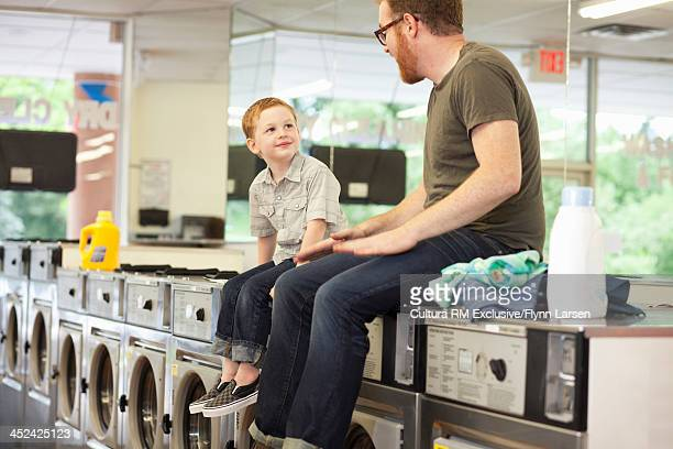 Father and son sitting on top of washing machines in launderette