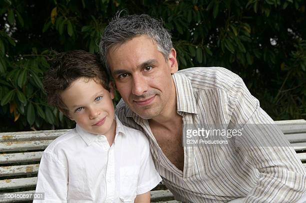 father and son (4-6) sitting on wooden bench, portrait, close-up - head cocked stock pictures, royalty-free photos & images