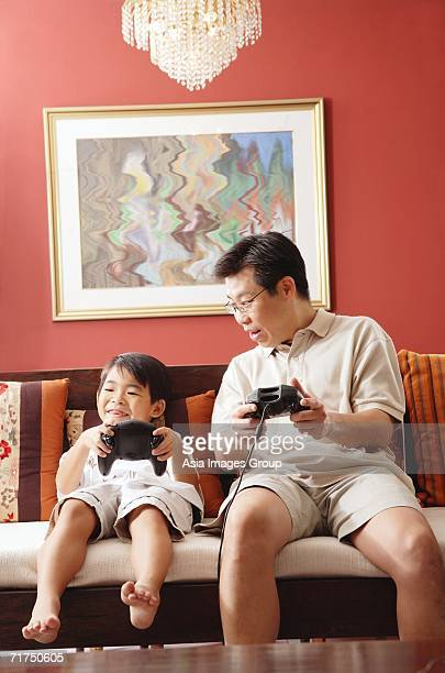 father and son sitting side by side on sofa, playing video game - バミューダパンツ ストックフォトと画像