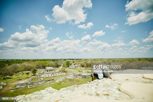 Father and son sitting together at top of pyramid while exploring Mayapan ruins