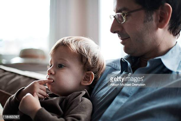 Father and son sitting together on couch