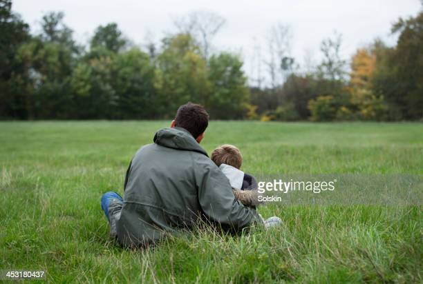 Father and son sitting together on grass field