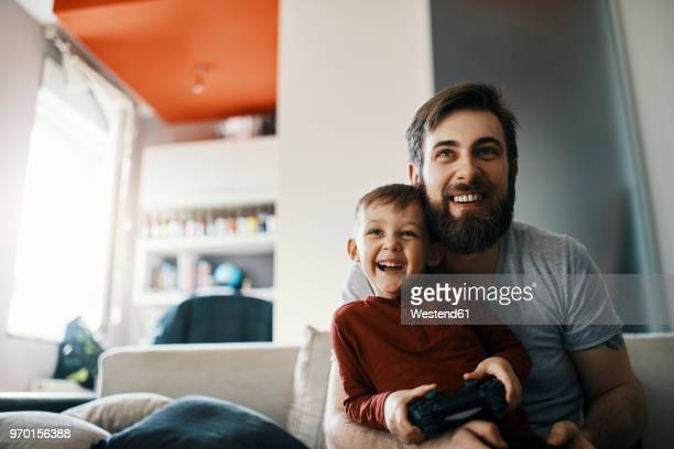 father and son sitting together on the couch playing computer game - son stock pictures, royalty-free photos & images